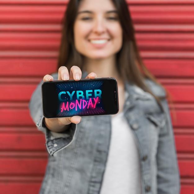Mujer mostrando teléfono inteligente con foto de cyber monday Foto gratis