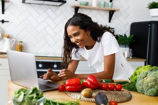 La mujer mulata bonita sonrió está mirando en la pantalla del portátil en la cocina moderna sobre la mesa llena de verduras y frutas, vestida con una camiseta blanca Foto gratis