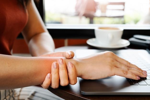 Mujer muñeca mano brazo dolor largo uso portátil trabajando. concepto de salud y medicina de síndrome de oficina Foto Premium