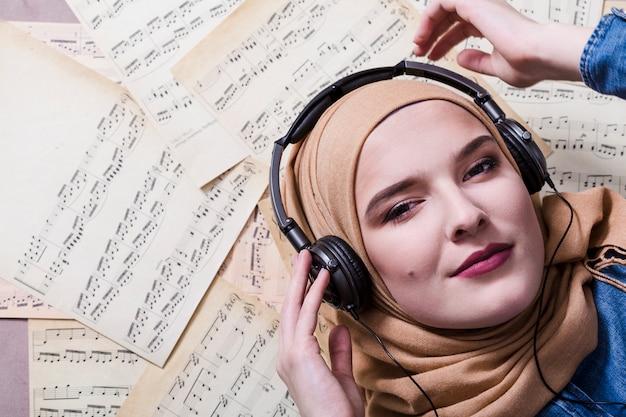 Mujer musulmana escuchando música en auriculares Foto gratis