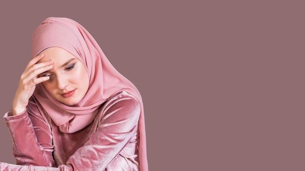 Mujer musulmana joven sola que mira abajo sobre el contexto coloreado Foto gratis
