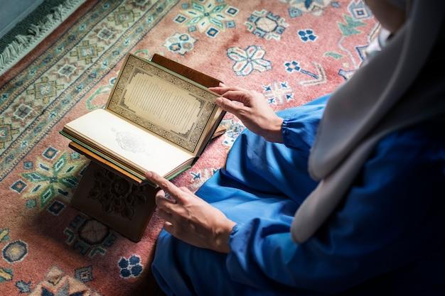 Mujer musulmana leyendo desde el corán Foto Premium
