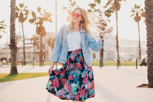Mujer muy sonriente caminando en las calles de la ciudad con elegante falda estampada y chaqueta vaquera de gran tamaño con gafas de sol rosas, tendencia de estilo veraniego Foto gratis