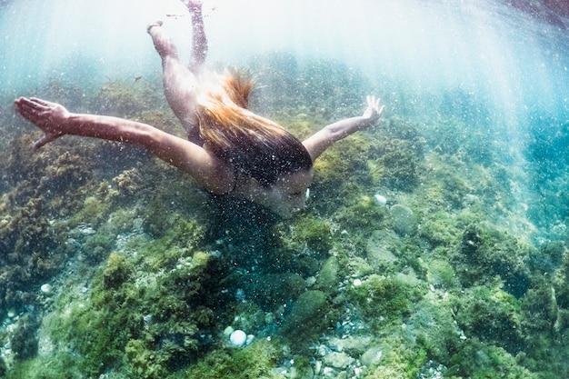 Mujer nadando bajo el agua Foto gratis