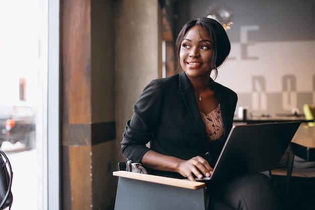 Mujer de negocios afroamericana trabajando en una computadora en un bar Foto gratis