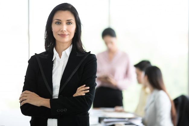 Mujer de negocios agraciada en el traje negro que se coloca con manera digna en oficina Foto Premium