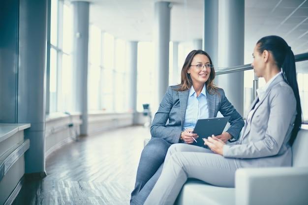 Mujer de negocios alegre hablando con su compañera Foto gratis