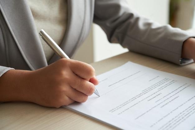 Mujer de negocios anónima recortada que comprueba el acuerdo antes de firmar Foto gratis