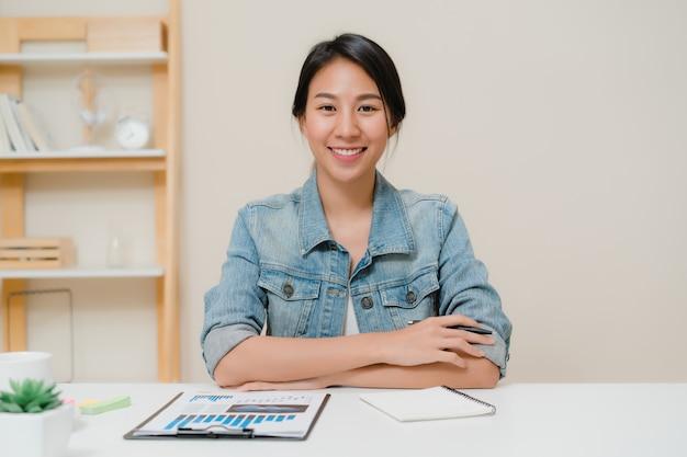 Mujer de negocios de asia que siente la sonrisa feliz y que mira a la cámara mientras que relájese en casa la oficina. Foto gratis