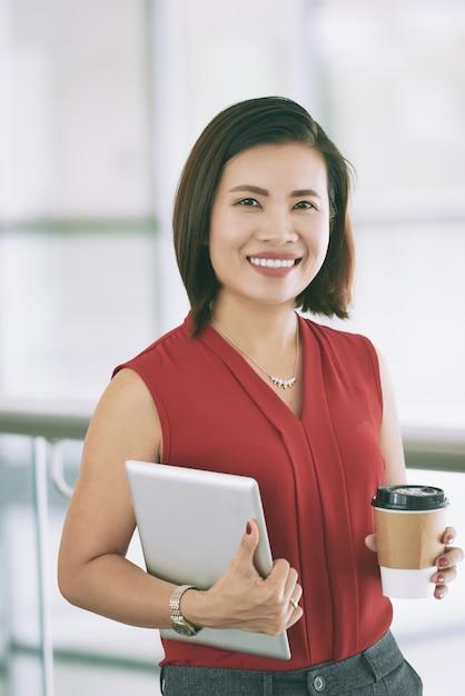 Mujer de negocios asiática confiada que presenta en el interior en el balcón con comida para llevar café y tableta Foto gratis