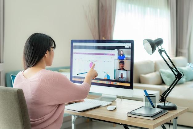 Mujer de negocios asiática hablando con sus colegas sobre el plan en video conferencia con el equipo de negocios usando la computadora para una reunión en línea en video llamada. Foto Premium