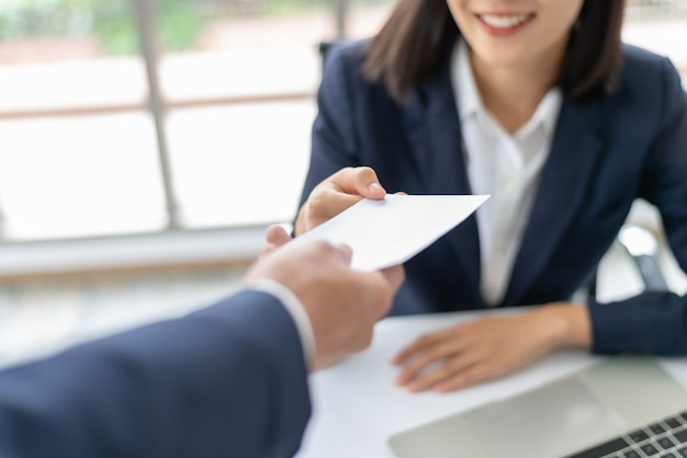 Mujer de negocios asiática joven que recibe dinero del sueldo o de la prima del encargado en la oficina. Foto Premium