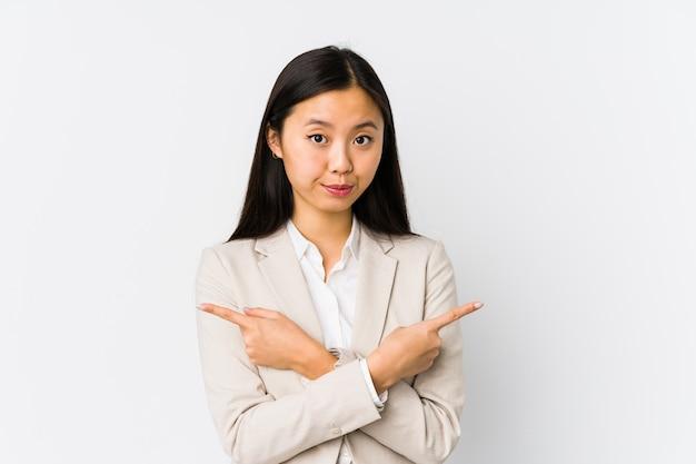 La mujer de negocios china joven aisló puntos de lado, está intentando elegir entre dos opciones. Foto Premium