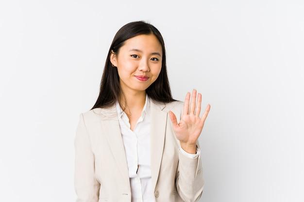 La mujer de negocios china joven aisló la sonrisa alegre que mostraba el número cinco con los dedos. Foto Premium