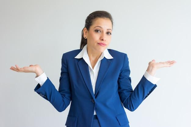 Mujer de negocios descuidada encogiéndose de hombros. Foto gratis