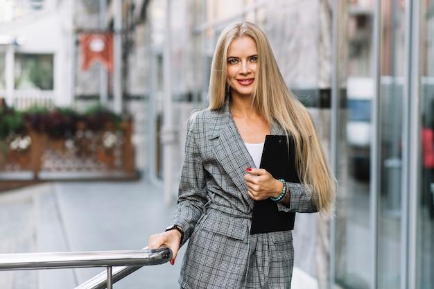 Mujer de negocios de estilo con portapapeles en ciudad Foto gratis