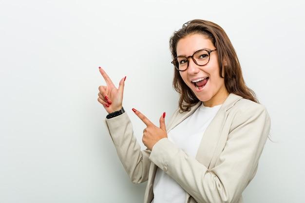 Mujer de negocios europea joven que señala con los dedos índices a una copia, expresando entusiasmo y deseo. Foto Premium