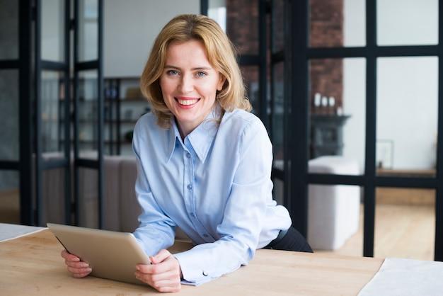 Mujer de negocios feliz que usa la tableta en la mesa Foto gratis