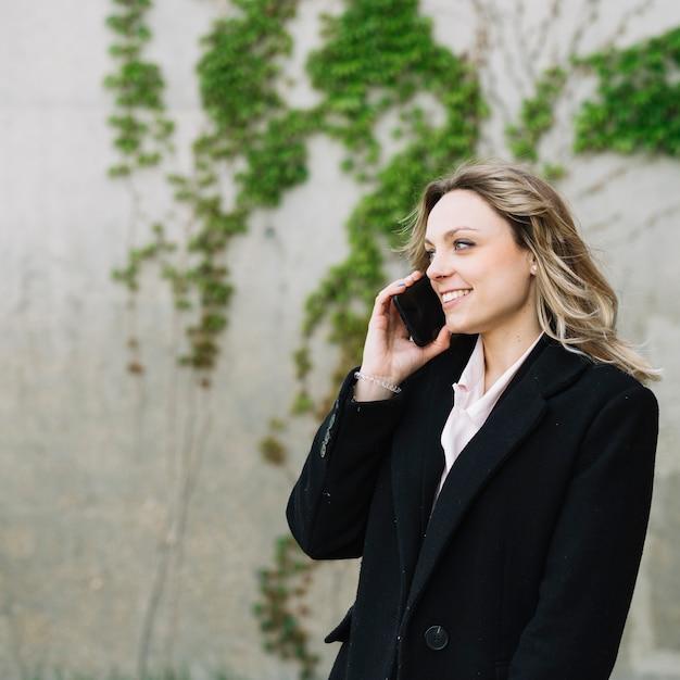 Mujer de negocios haciendo llamada al aire libre Foto gratis