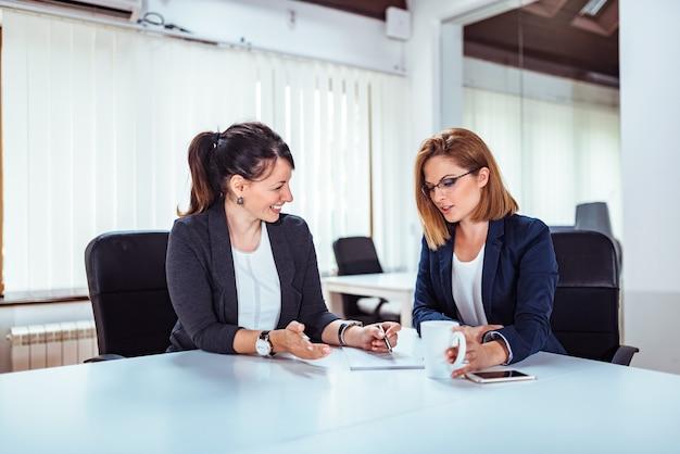 Mujer de negocios hermosa dos que habla en la sala de conferencias. Foto Premium