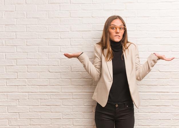 Mujer de negocios joven bonita empresaria confundida y dudosa Foto Premium