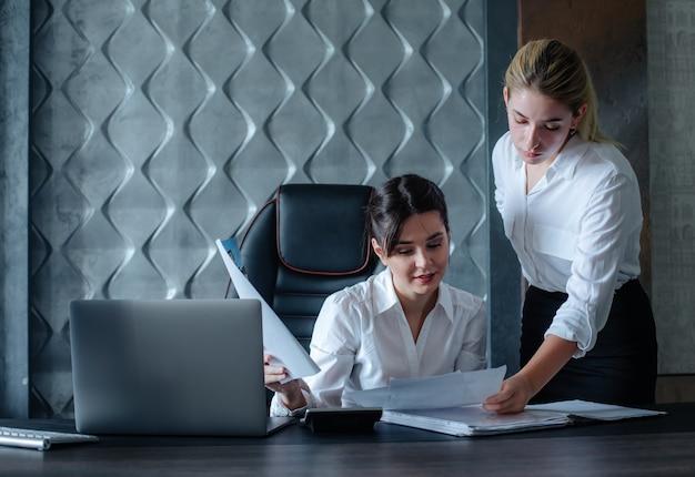Mujer de negocios joven directora sentada en el escritorio de oficina con documentos de proceso de trabajo reunión de negocios trabajando con un colega para resolver tareas comerciales concepto colectivo de oficina Foto gratis