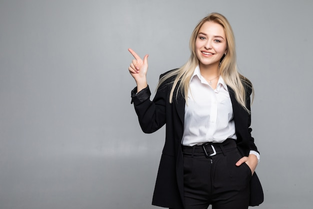 Mujer de negocios joven que señala el dedo al lado en la pared gris aislada Foto gratis