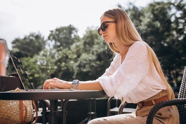 Mujer de negocios joven que trabaja en la computadora portátil afuera en un café Foto gratis