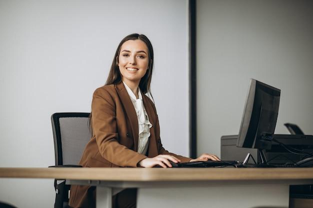 Mujer de negocios joven que trabaja en la computadora portátil en la oficina Foto gratis