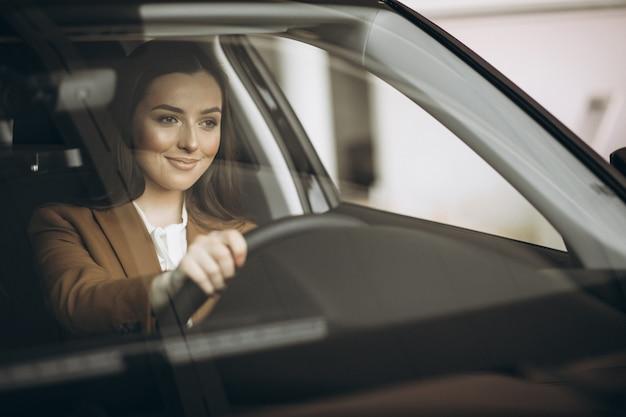 Mujer de negocios joven sentada en el coche Foto gratis