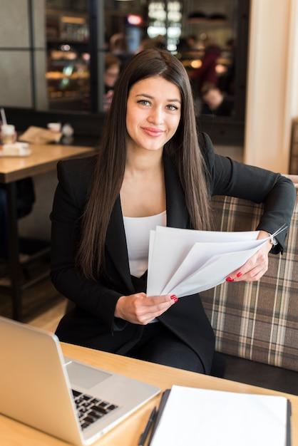 Mujer de negocios leyendo documento Foto gratis
