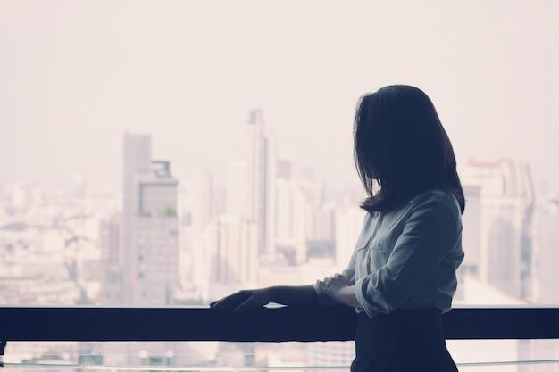 Mujer de negocios mirando a la vista de la ciudad Foto Premium