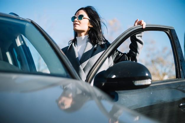 Mujer de negocios moderna de pies al lado de coche Foto gratis