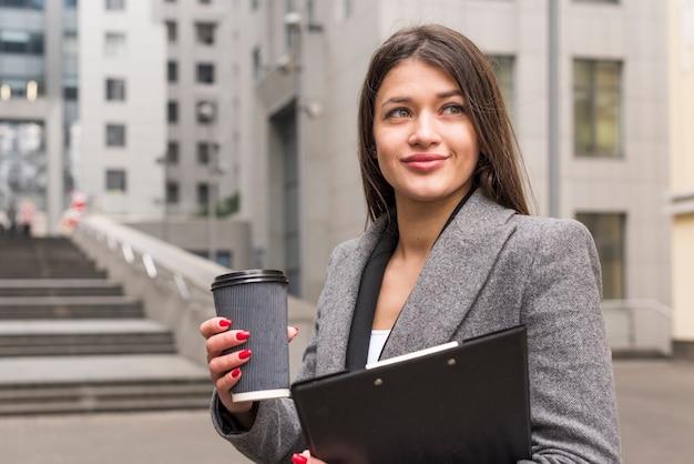 Mujer de negocios morena con café Foto gratis