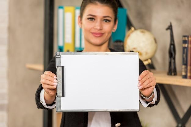 Mujer de negocios morena enseñando papel Foto gratis
