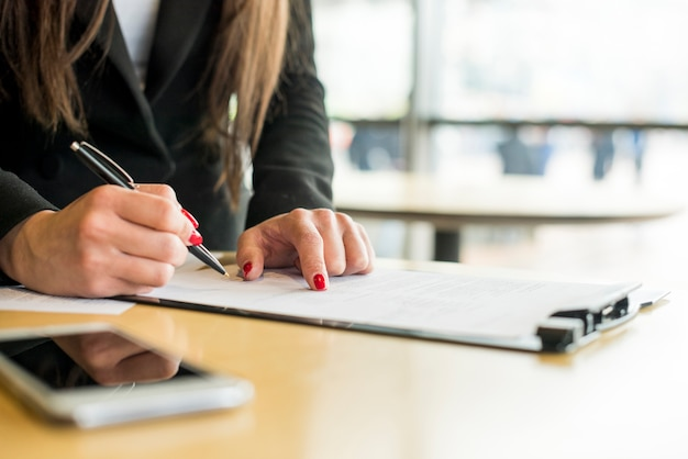 Mujer de negocios morena escribiendo en un documento Foto gratis