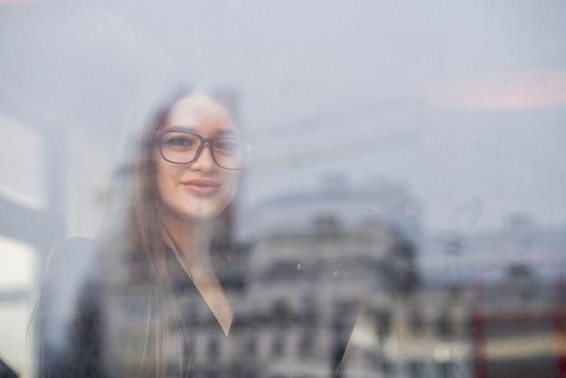 Mujer de negocios morena a través de un cristal Foto gratis