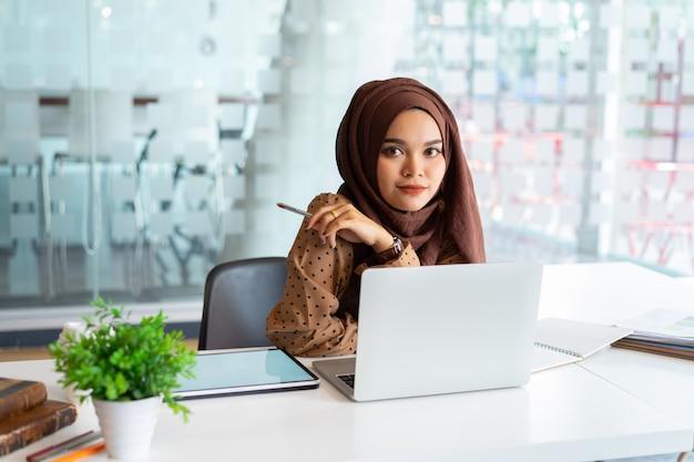 Mujer de negocios musulmana asiática joven en ropa casual elegante, negocios y sonriendo mientras está sentado en el coworking creativo. Foto Premium