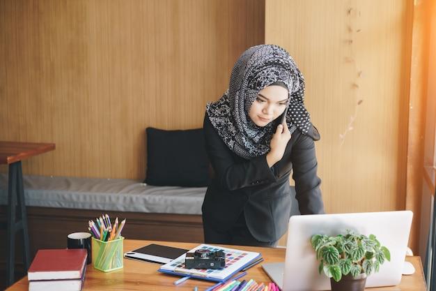 Mujer de negocios musulmana asiática ocupada hablando por teléfono móvil y usando la computadora portátil en la oficina moderna. Foto Premium