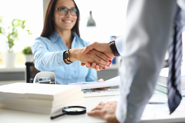 La mujer de negocios en oficina sacude las manos con el socio comercial. Foto Premium