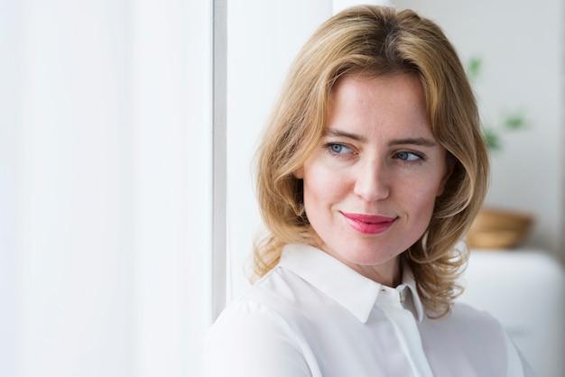 Mujer de negocios pensativa en la camisa blanca Foto gratis