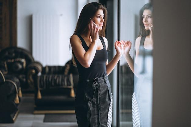 Mujer de negocios que habla en el teléfono que hace una pausa la ventana Foto gratis