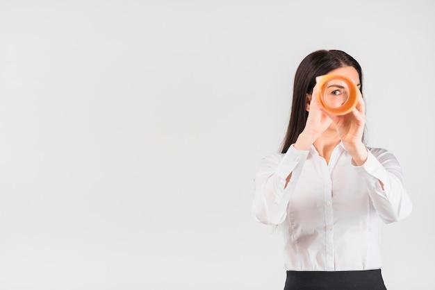 Mujer de negocios que mira a través del rollo de papel Foto gratis