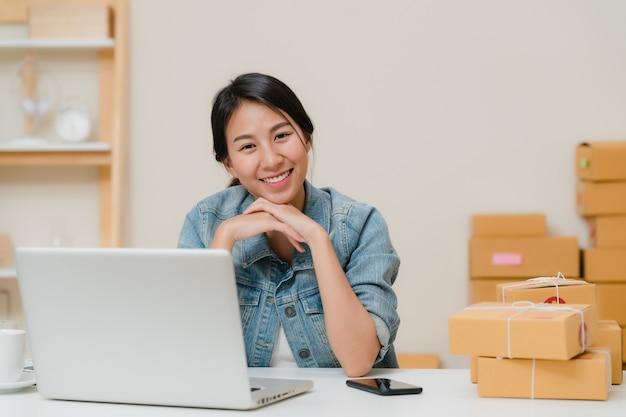 Mujer de negocios que siente la sonrisa feliz y que mira a la cámara mientras que trabaja en su oficina en casa. Foto gratis
