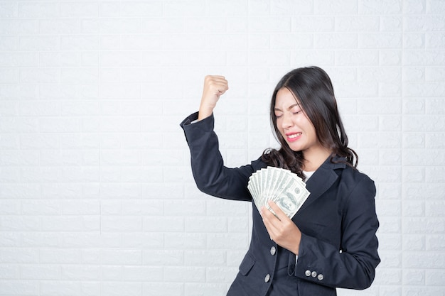 La mujer de negocios que sostenía el billete de banco, cobraba por separado, pared de ladrillo blanca hizo gestos con lenguaje de signos. Foto gratis