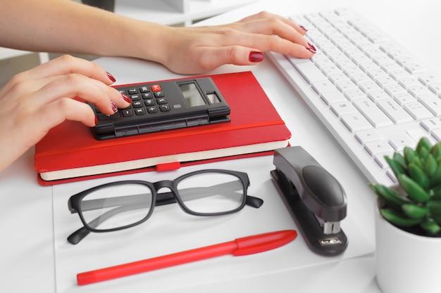 Mujer de negocios que trabaja con datos financieros mano usando calculadora Foto Premium