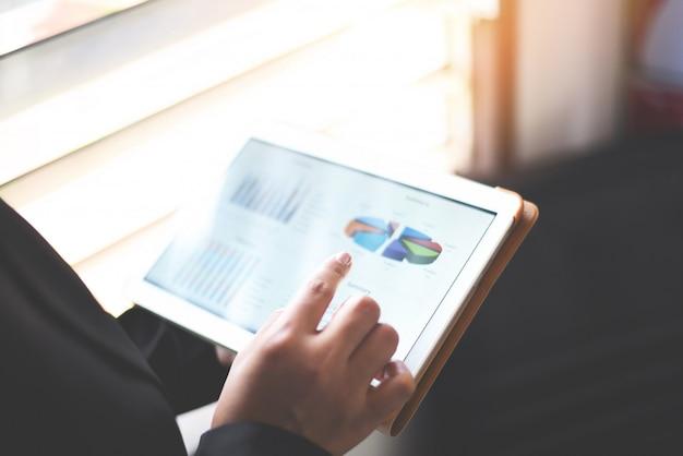 Mujer de negocios que trabaja que comprueba la tableta del informe de negocios usando el dinero de la tableta que analiza gráficos Foto Premium