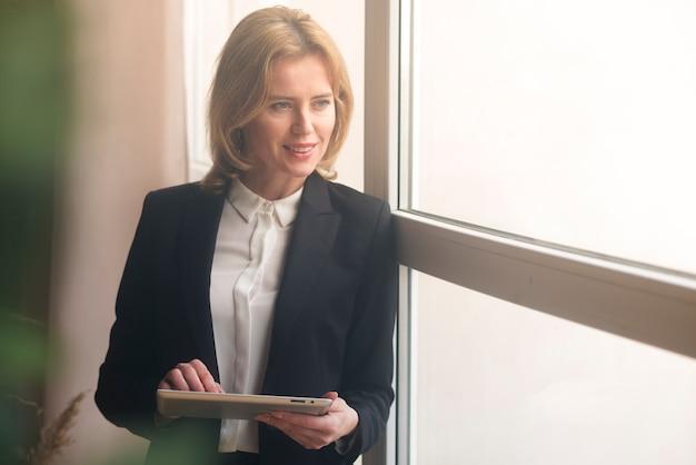 Mujer de negocios que usa la tableta en la ventana Foto gratis
