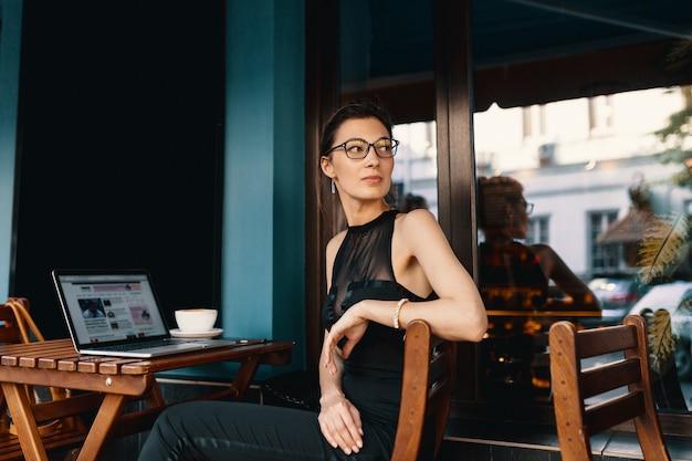 Mujer de negocios refinada en vasos, sentado a la mesa en el trabajo de café Foto gratis