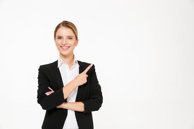 Mujer de negocios rubia sonriente que señala lejos sobre blanco Foto gratis